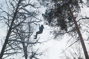 Adventure climbing high wire park - man in helmet and safety equipment at winter day