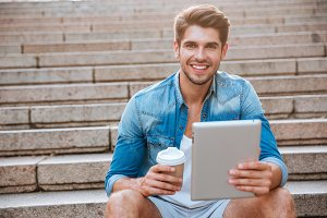 Happy cheerful student with tablet and coffee cup sitting outdoors