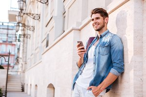 Smiling happy casual man using mobile phone outdoors