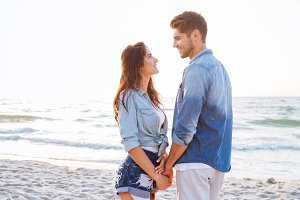 Couple standing and holding hands on the beach