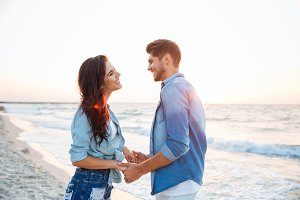 Couple holding hands and laughing on the beach