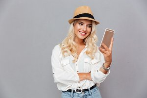 Smiling young woman typing message on mobile phone