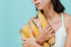Sad pretty young woman standing and holding corn cobs