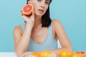 Beautiful young woman sitting and holding half of grapefruit