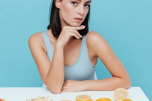 Beautiful woman sitting at the table with oranges and grapefruits