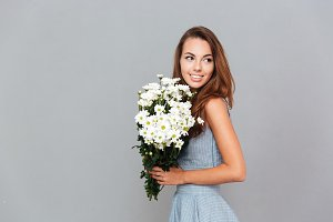Happy pretty young woman with bouquet of flowers