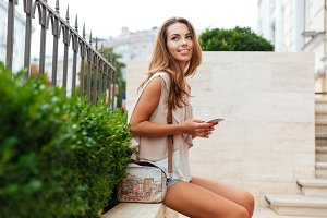 Smiling cheerful woman resting and holding mobile phone outdoors
