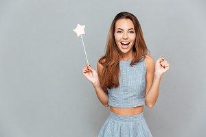 Happy amazed young woman holding magic wand