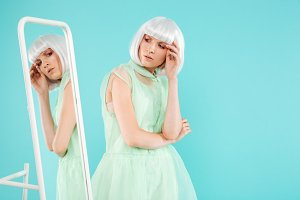 Woman in blonde wig standing and posing near the mirror