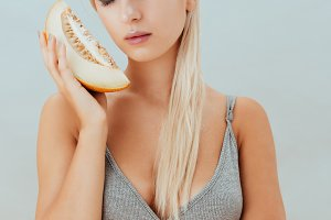 Attractive young woman with stylish makeup holding slice of melon
