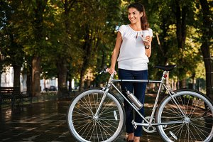 Smiling young woman drinking takeaway coffee and holding bicycle