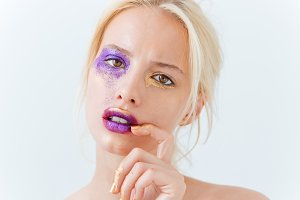 Beauty portrait of young female with purple fashion makeup