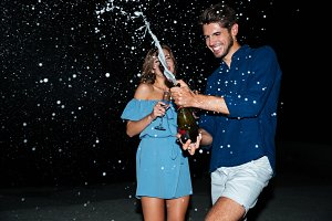 Cheerful young couple drinking champagne and having fun at night
