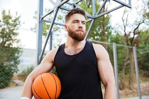 Portrait of a bearded basketball player standing with ball