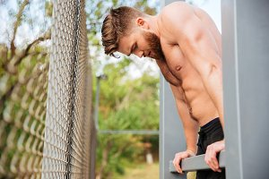 Hnadsome shirtless bearded sportsman doing workout