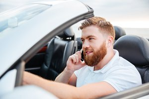 Young man driving his car and speaking on the cellphone