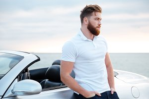 Handsome bearded man in white shirt leaning on car outdoors
