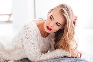 Attractive blonde woman with red lipstick laying on the floor
