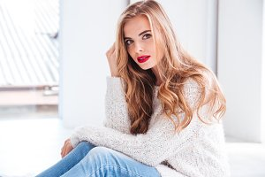 Attractive woman wearing sweater and red lipstick looking at camera