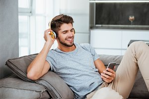 Man in headphones listening to music while lies on sofa