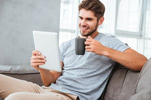 Cheerful man communication by tablet while drinking a coffee