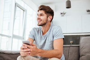 Happy man listening to music while sitting on sofa