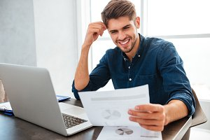 Young cheerful man sitting at home while looking on paper