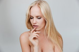 Serious blonde girl with closed eyes posing