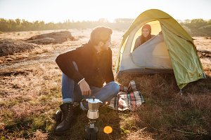 Young man making coffee for his girlfriend in a tent. Traveling together.