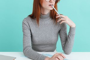 Attractive redhead young woman in round glasses sitting and reading
