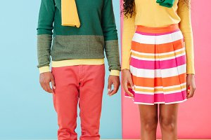 Cheerful african american young couple in scarves and hats standing