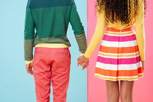 Back view of beautiful african couple standing and holding hands