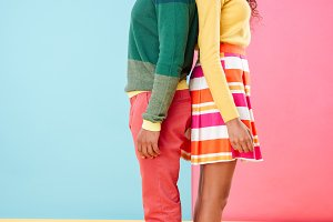 Beautiful african young couple standing over colorful background