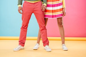 Legs of young couple in bright clothes standing together