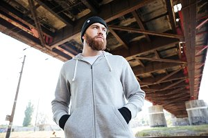 Young casual bearded man in hat standing under urban bridge
