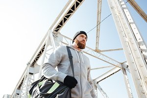Portrait of an athlete with sports bag walking along bridge