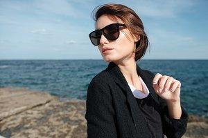 Cute young woman in sunglasses walking near the sea