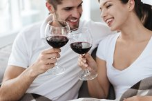 Couple sitting and drinking wine at home