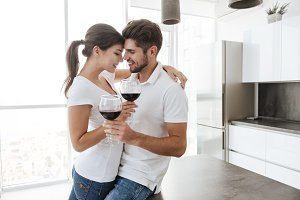 Sensual couple hugging and drinking red wine on the kitchen