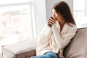 Pensive woman thinking and drinking coffee at home