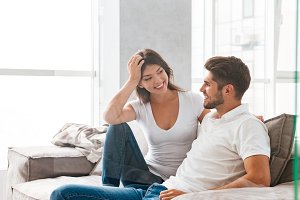 Cheerful beautiful young couple sitting and talking on sofa