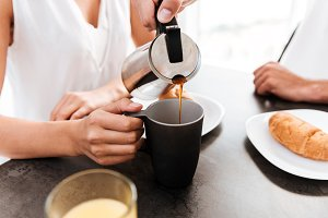 Man pouring coffee into cup of his girlfriend on kitchen