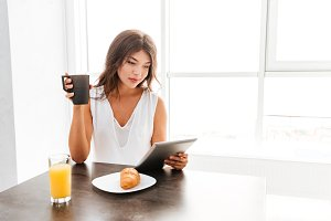 Smiling woman using tablet and having breakfast at home