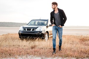 Serious young casual man walking near his car outdoors