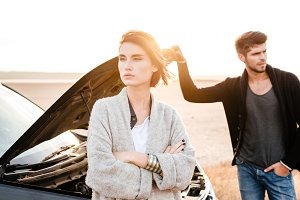 Young couple standing near broken car with open hood outdoors