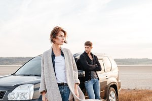 Young travelers couple standing near car outdoors