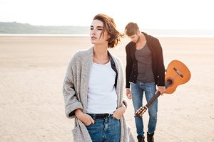 Beautiful young couple standing at the seashore with guitar