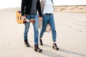 Casual couple walking at the beach with guitar