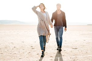 Romantic young couple walking on the seaside in autumn