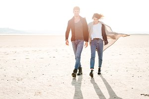Full length portrait of smiling happy couple walking along seashore